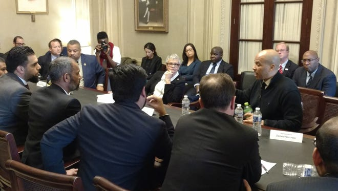 Sen. Cory Booker, right, reacts to stories about intolerance and intimidation experienced by New Jersey Muslims at a discussion that brought Muslim leaders and members of the state's delegation together in the Capitol. 2/14/17