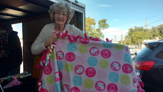 Mary Lou Beard holds up one of the hundreds of blankets made by her quilting friends in Ohio.