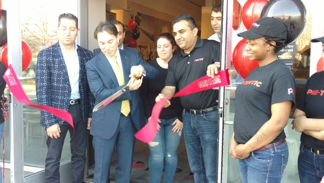 East Brunswick Mayor Brad Cohen, who hosted an official ribbon-cutting ceremony Wednesday for Pie Five Pizza Co., cuts the ribbon as store owner, Dinesh Goswami, holds the other end. To Goswami's right is East Brunswick Regional Chamber of Commerce's Lillian Feldman, also the owner of Pinot's Palette of East Brunswick.