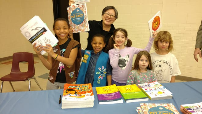 Local author Janet Wong poses with kids.