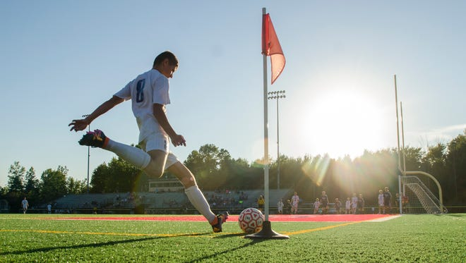 Saints' Derek McComas kicks from the corner Monday, Sept. 19, during a soccer match against Marysville at East China Stadium.