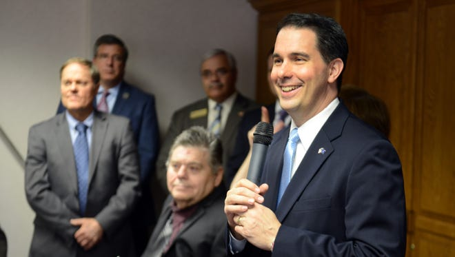 Wisconsin Gov. Scott Walker, right, has said he would call the state legislature into special sesion if courts ruled against the state's voter identification law.