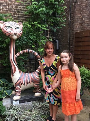 Reporter for The News Leader Monique Calello and her daughter Emma pose beside the tiger sculpture inside The Smith Center's Mevluda Tahirovic Memorial Garden in Staunton. In February 2016, Calello's life partner passed away, and she found the garden a source of comfort. It was while spending time there that she began to wonder about the names engraved in bricks, especially Tahirovic's name inscribed on the headstone at the center of the garden.