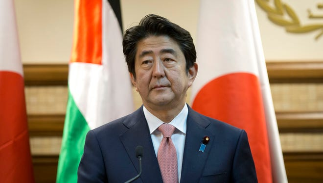 Japanese Prime Minister Shinzo Abe attends a joint press conference with Palestinian President Mahmoud Abbas at the Palestinian Authority headquarters, in the West Bank city of Ramallah, Tuesday, Jan. 20, 2015. An online video released Tuesday purported to show the Islamic State group threatening to kill two Japanese hostages unless they receive a $200 million ransom in the next 72 hours.