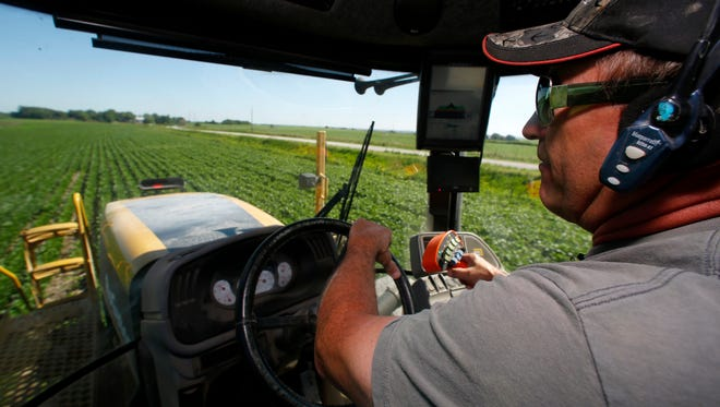 Danny Dammann runs a sprayer across a Montgomery County soybean field in July. The sprayer is guided by a Global Positioning System.