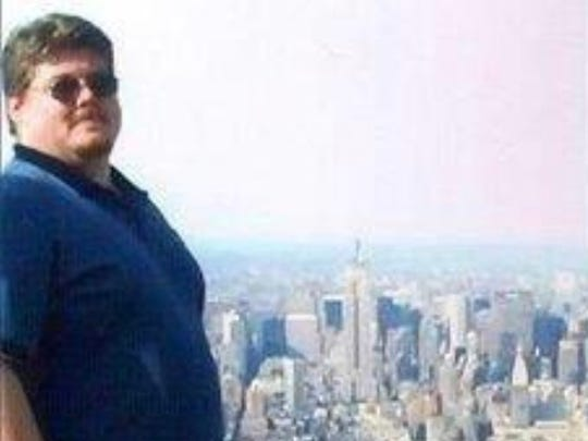 """John """"Johnny"""" Bulaga Jr. standing atop tower one of the World Trade Center with the city down below him in the background. The photograph was taken on May 1, 2001, just four months before the 9/11 attacks."""