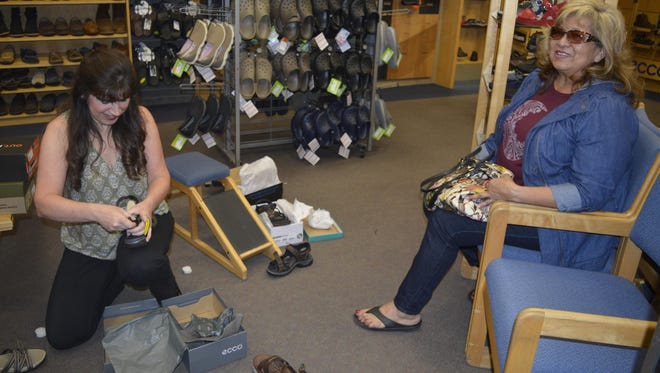 Margaret Beair, a 17-year employee, helps customer Martina Beltran pick out some shoes Wednesday at Feet For Life, a men's and women's health and welless and pedorthic footwear store in the Visalia Mall.