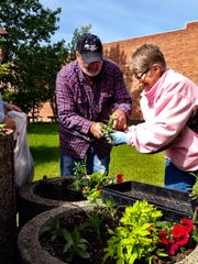 Dan Ross, Mark Mikeson and Sheila Dixon plant flowers in Basin Park in Stanford. About a dozen volunteers helped beautify the town on the June 12 planting day.