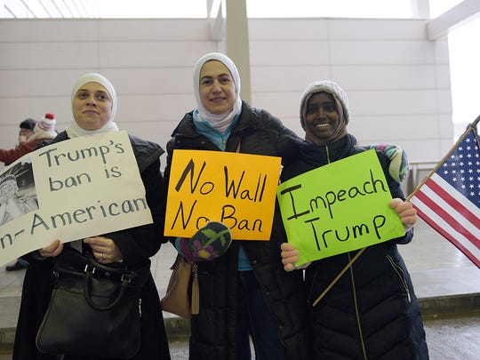 Deena Kashlan (from left), Ranya Shbeib and her daughter Farhiya Issac of Bloomfield Hills were among the protesters Sunday at Detroit Metropolitan Airport.