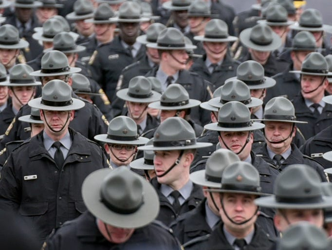 Troopers march towards their vehicles during a funeral