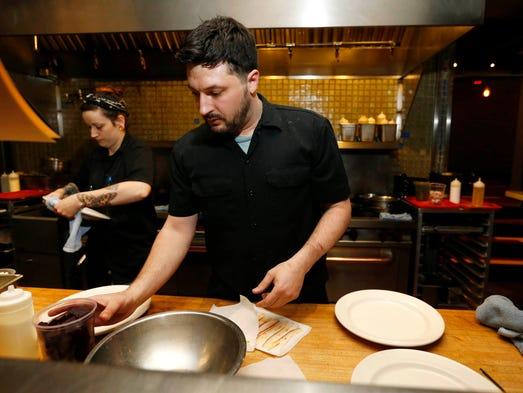 Chef Joe Tripp grabs ingredients as he works on a tasting