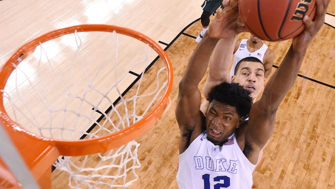 Duke's Justise Winslow (12) is fouled by Michigan State's Gavin Schilling.