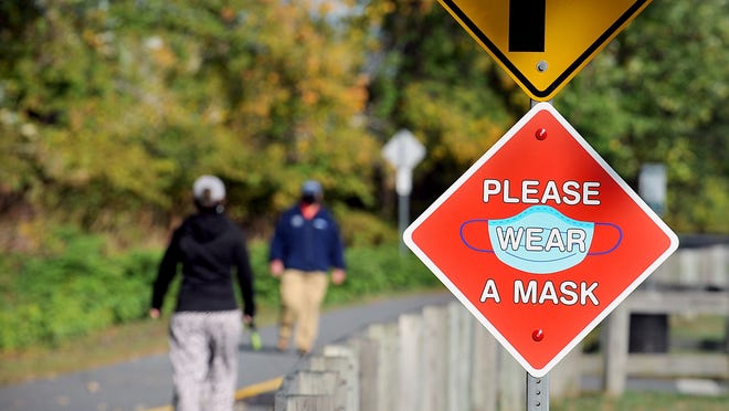 A sign along the Upper Charles Rail Trail at Fino Field in Milford urges mask use.
