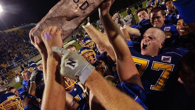 SDSU players are the first to hoist the Dakota Marker trophy in 2004 after beating NDSU at Coughlin-Alumni Stadium.