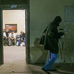 Stuart Carter, 57, walks towards the East Lot while Dee Saafir (left), 36, Henry Harding (center), 40 and Kevin Wheeler, 57, sit inside the Mens Overflow Shelter February 4, 2015. The East Lot is a parking lot that serves as Maricopa County's current solution for emergency shelter. The shelter closed at the end of March.