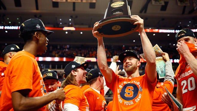 Trevor Cooney #10 of the Syracuse Orange raises the regional trophy.