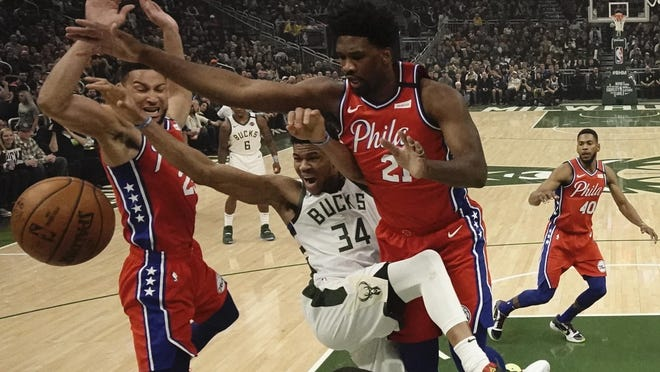 The Sixers' Joel Embiid, right, and Ben Simmons double-team the Bucks' Giannis Antetokounmpo.