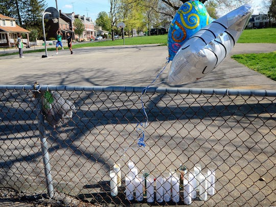 A trio plays basketball in Girard Park near a memorial created for Oscar Cherry III, Tuesday, April 18, 2017. Cherry was assaulted Monday night at the park and died of his injuries Tuesday morning. A suspect has been arrested. John A. Pavoncello photo