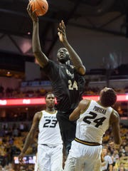 Missouri's Kevin Puryear, right, draws a foul from Central Florida's Tacko Fall, center, as Jeremiah Tilmon, left, looks on during overtime of an NCAA college basketball game Sunday, Dec. 2, 2018, in Columbia, Mo. Missouri won the game 64-62. (AP Photo/L.G. Patterson)