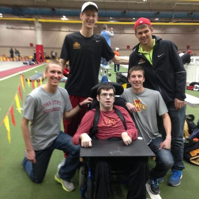 Members of Iowa State's track team surround Andy Ackermann