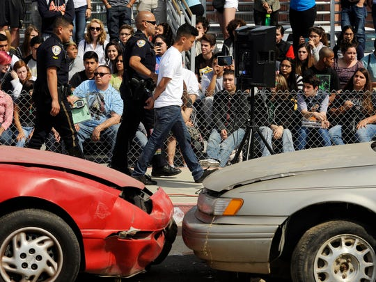 """In a simulated collision- Golden West student Jose Chavez, 17, center, is evaluated for his blood alcohol level, and was found to be under the influence and is taken into custody. Golden West students watch and some participate Tuesday morning in the """"Every 15 Minutes"""" program, a simulated drunk driving collision scene, at the Golden West High School parking lot. In the simulated two-car and a bicycle collision, a student driving to school drunk killed a teacher and two fellow students."""