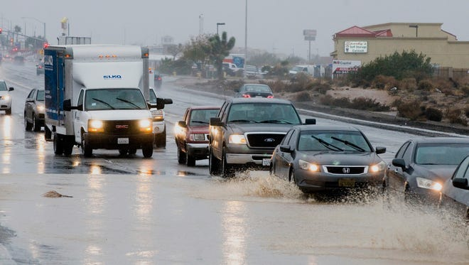 Traffic moves around flooding in the right lane of main Street in Hesperia, Calif., on Dec. 12.