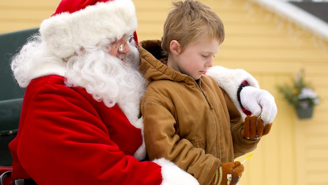 Brayden Hephner, 5, of Wisconsin Rapids receives a piece of candy from Santa Claus at Rudolph Country Christmas, Saturday, Dec. 13, 2014.