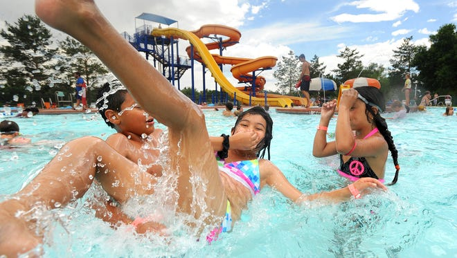 Antony Raiz throws Maria Novoa into the water as Jenny Trejo, at right, watches during a La Familia outing on Wednesday, June 27, 2012, at City Park Pool in Fort Collins.