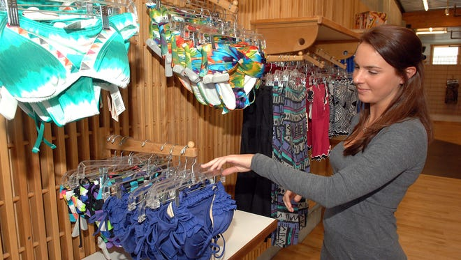 South Moon Under in Rehoboth Beach is a  business that sells beach items year-round. Sales Associate Katelyn Buchwald goes through some of their new swimsuits in this 2010 file photo.