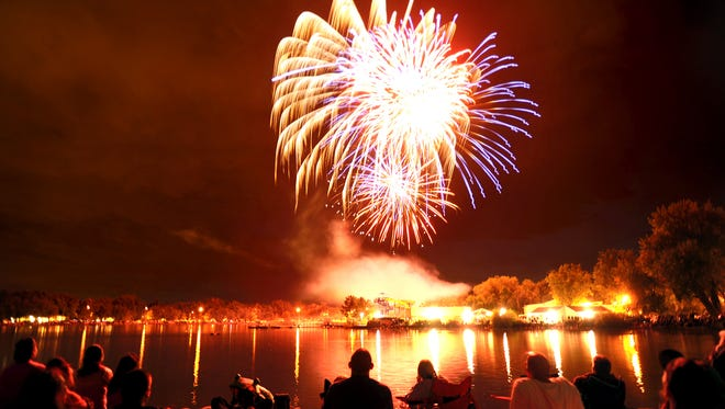 People line the shore of Sheldon Lake in Fort Collins as Independence Day fireworks explode over the water in 2012.