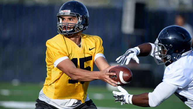 Nevada quarterback Tyler Stewart hands the ball to running back James Butler during spring camp. The Wolf Pack will have a new offense but will still use part of the Pistol offense.