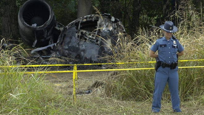 Lexington police Officer Adrienne Thomasson stood by a piece of wreckage from Comair Flight 5191. Media representatives were escorted to the crash site, where the smell of jet fuel lingered. August 29, 2006