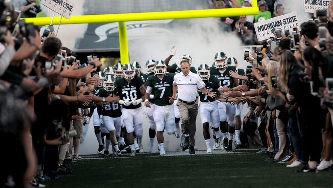Head coach Mark Dantonio leads the Spartans onto the field before the first half of play against Furman in the Spartan's opening game of the 2016 season on Friday.