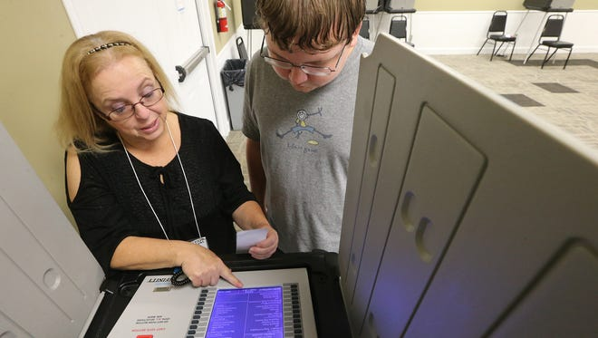 Poll worker Joyce Kittle, left, shows Evan Valdez the voting procedure before he votes at the Middle Tennessee Association of Realtors on Thursday, Nov. 3, 2016, the last day of early voting.
