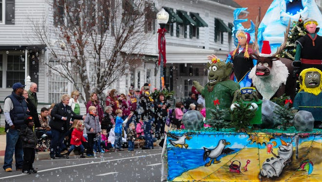 Children play in  bubbles floating from ECI's Frozen-themed float in Princess Anne during the annual Christmas Parade.