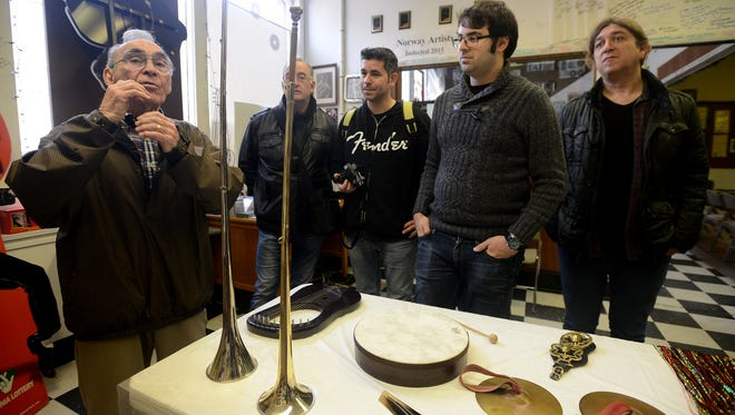 Henry Harrison shows members of the Spanish band Tremendos a collection of musical instruments of the Bible on display at the International Rock-A-Billy Hall of Fame on Tuesday afternoon.