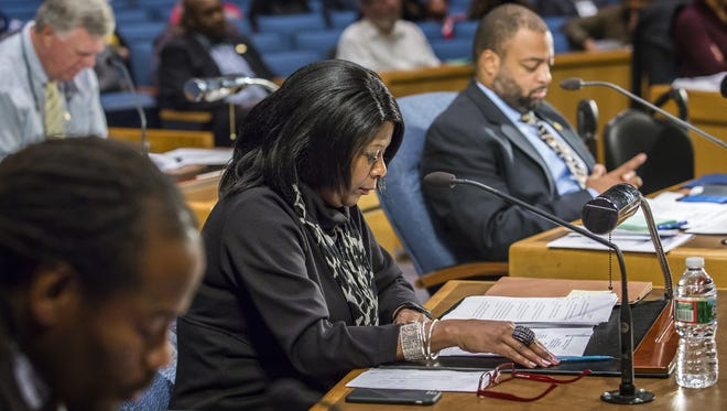 Councilwoman Zanthia Oliver sits with other members of the Wilmington City Council in silent reflection at the start of the city council's meeting on Thursday night.