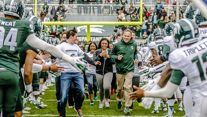 Michigan State coach Mark Dantonio, running onto the field with MSU students before a spring game in Spartan in 2015.