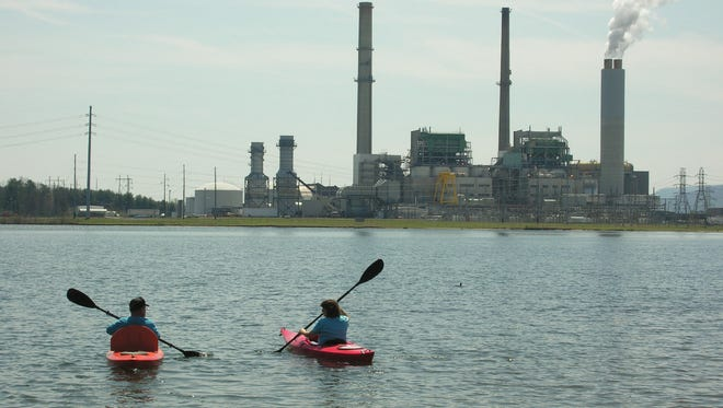 Paddlers head out onto Lake Julian across the lake from the Duke Energy plant. The coal-burning plant is set to be retired by 2019.