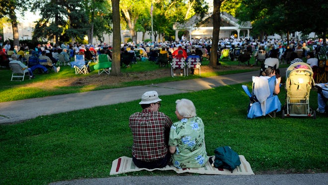 A couple cuddles on a blanket as they listen to the Green Bay City Band during their concert at St. James Park in Green Bay on June 30, 2010.