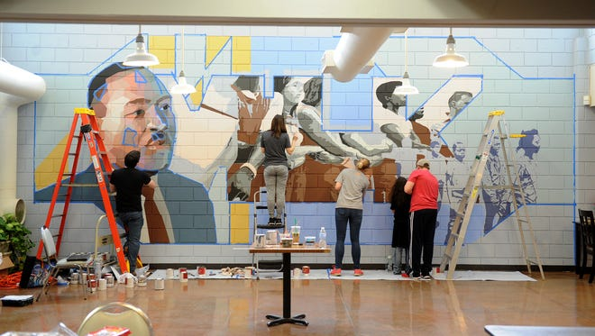 Volunteers work on the Martin Luther King mural Saturday, Dec. 30, 2017, at the Martin Luther King Center.