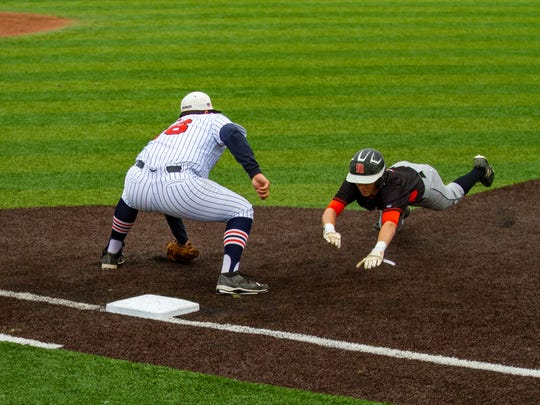 Sam Mongelli dives back to first base to avoid the