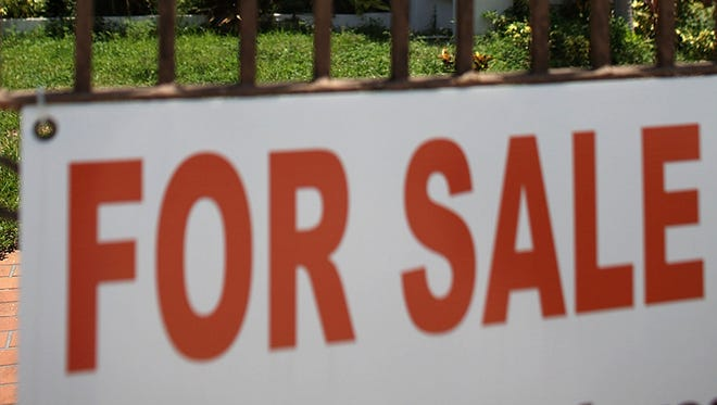 A For Sale sign is displayed in front of a home.