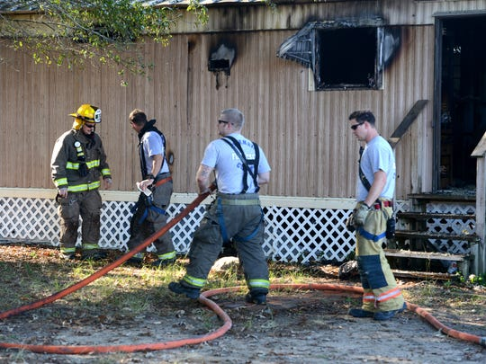Escambia County Fire Rescue firefighters wrap up working a mobile home fire in 2014 off Pine Forest Road.