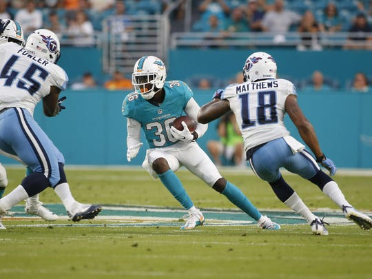 Miami Dolphins defensive back Tony Lippett (36) intercepts a pass as Tennessee Titans wide receiver Rishard Matthews (18) and fullback Jalston Fowler (45) attempt to tackle during the first half of an NFL preseason football game against the Tennessee Titans, Thursday, Sept. 1, 2016 in Miami Gardens, Fla. (AP Photo/Wilfredo Lee)
