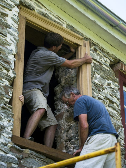 Chris Lainhoff of Museum Quality Building Restorations, and Tom Lainhoff, right, fit a new window frame Friday for the Alexander Schaeffer farm house. Historic Schaefferstown Inc. received a 50,000 matching grant from the Pennsylvania Historical and Museum Commission, which will be used to replace 17 windows and two door frames at house. See more photos at photos.ldnews.com.