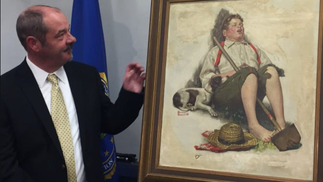 John Grant examines the Norman Rockwell painting stolen from his childhood home in Cherry Hill in 1976.
