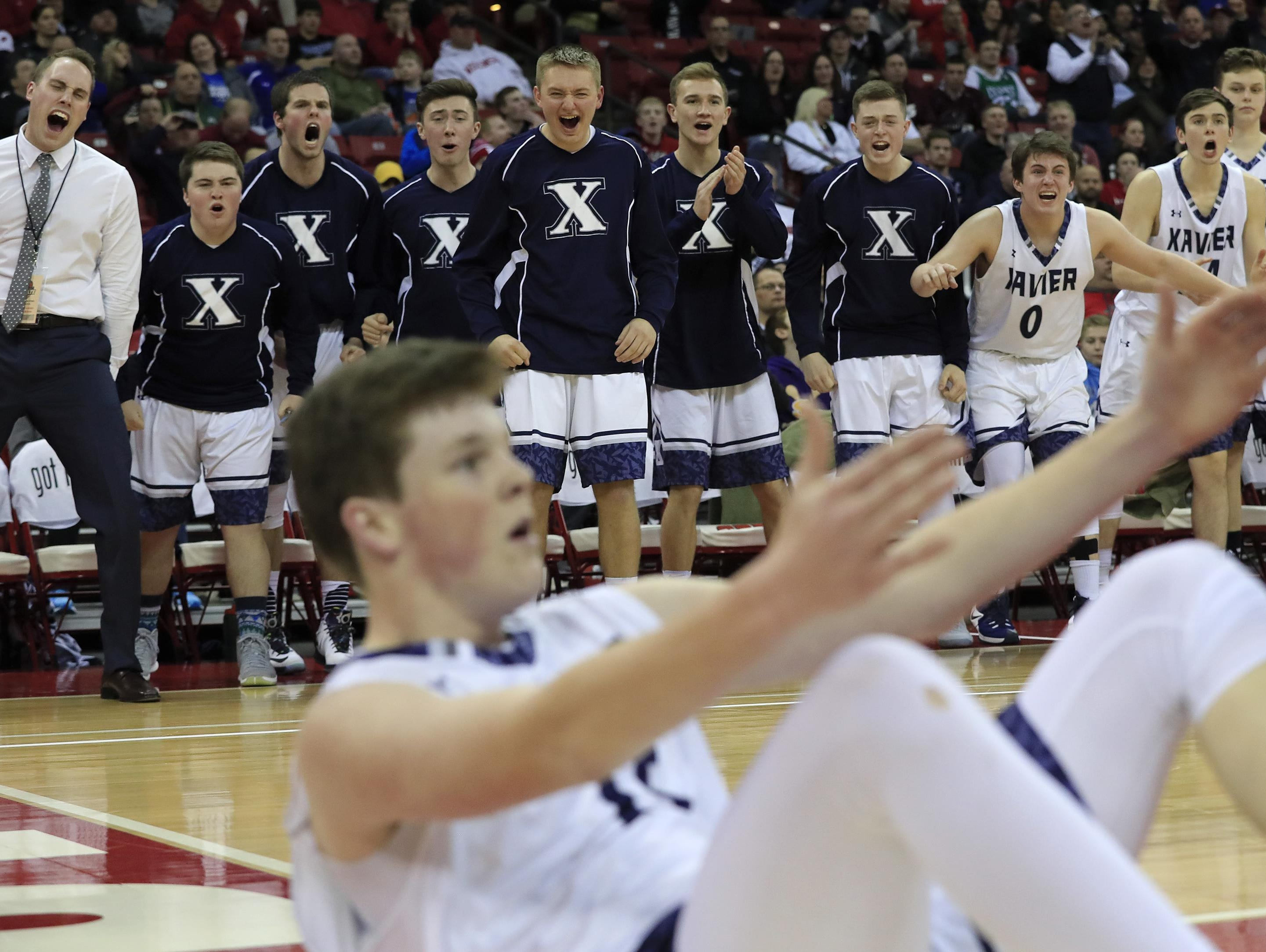 Xavier's bench reacts after Nate DeYoung (15) drew a foul on Prescott's Owen Hamilton (33) in the WIAA Division 3 championship game at the boys basketball state tournament at the Kohl Center on Saturday. Xavier won the game, 73-47.