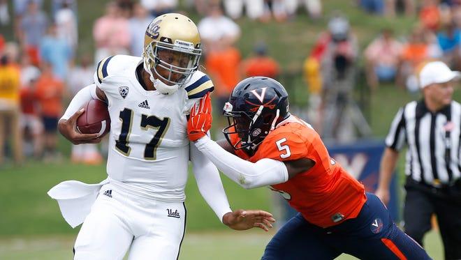 Aug 30, 2014: UCLA quarterback Brett Hundley (17) runs with the ball as Virginia Cavaliers cornerback Tim Harris (5) defends in the first quarter at Scott Stadium.