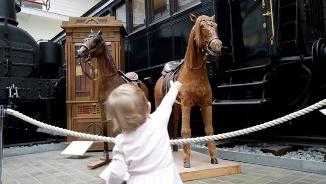 In this picture taken on Thursday, Feb. 23, 2017, a young girl looks at restored stuffed horses that were part of a historical carousel put on display at the National Technical Museum in Prague, Czech Republic. The museum acquired the carousel in 2004 from its private owners and had finally secured enough money to finance a major renovation project.
